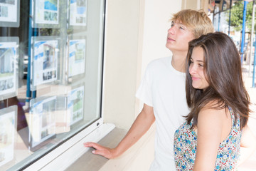 young couple look Real Estate Offers in street