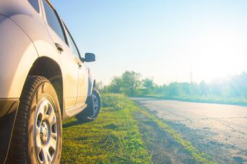 Car by the asphalt road at sunrise