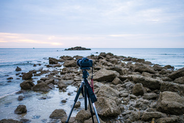 Camera on tripod shooting sunrise with seascape view
