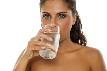 a young woman drinks cold water from the glass