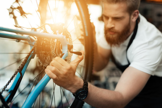 A young guy repairs a bicycle.