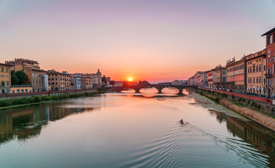 Sunset time in Florence, Italy. Bright sky over Arno river and medieval bridge.