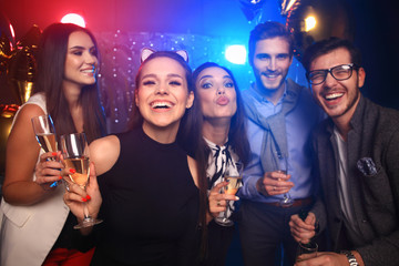 Enjoying amazing party. Group of beautiful young people dancing with champagne flutes and looking happy.