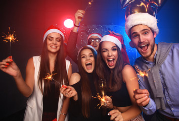 Celebrating New Year together. Group of beautiful young people in Santa hats throwing colorful confetti, looking happy