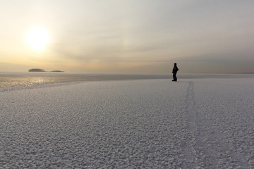 Man standing on the thin ice of a freezing pond and looking at the island, Ob reservoir, Siberia, Russia