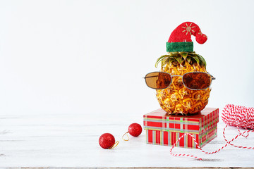 Closeup of pineapple in sunglasses and red hat with christmas decorations over white background. Copy space. Christmas in exotic country concept.