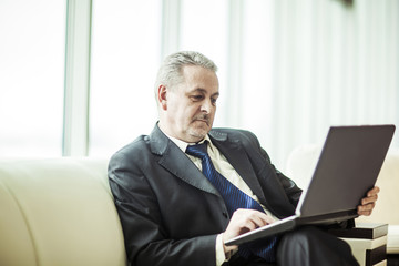 experienced businessman working on laptop sitting on sofa in a private office