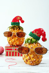 Closeup of two pineapples in sunglasses and red hat with christmas decorations over white background. Copy space. Christmas in exotic country concept.
