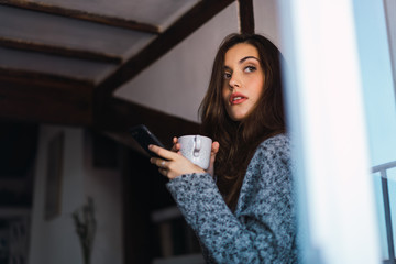 Beautiful model with cup of coffee and smartphone