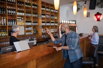 Man ordering a wine bottle at bar counter