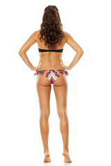 Back view of young pretty brunette posing in bikini on white background
