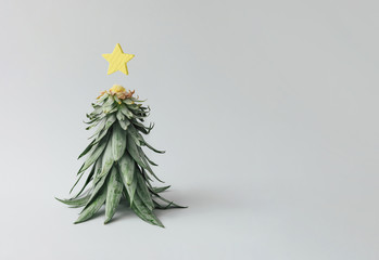 Christmas tree made of pineapple leaves and christmas decoration. Holiday concept.