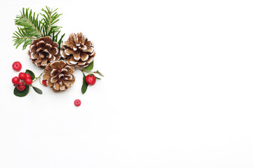 Christmas festive styled stock image floral composition. Pine cones, fir tree branches and red gaultheria berries on white wooden background. Flat lay, top view with empty copy space.