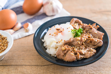 stir-fried pork with garlic on topped rice with egg