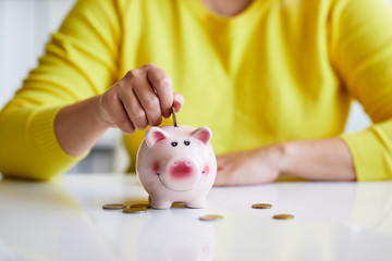 Close up of female hand putting coin into piggy bank