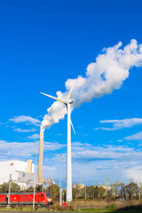 A wind turbine and a factory pipe with smoke.