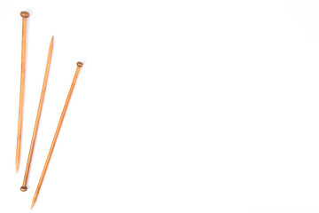 Wooden knitting needles on white background.