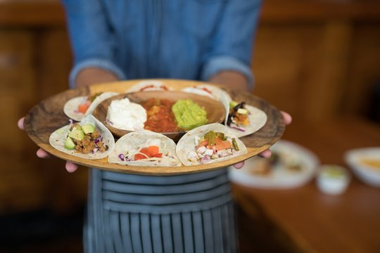 Waiter holding plate of Mexican food in bar