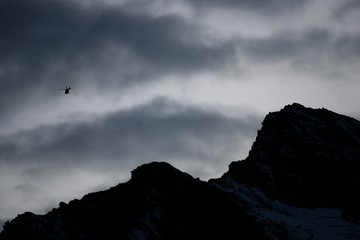 Rescue helicopter fly in Swiss Alps at sunset