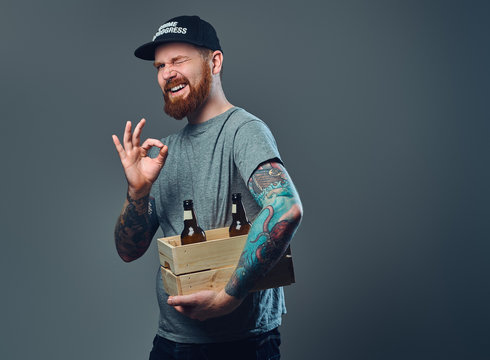 A man holds a wooden box with beer bottles.