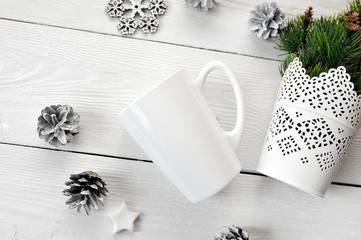Mockup white cup on a wooden background, in Christmas decorations. The top view is photographed