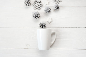 Mockup white cup with christmas cones and stars, on a white wooden background. Flat lay, top view photo mock up