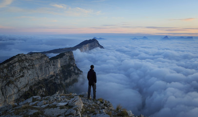 Fotomurales - Man looking over a sea of clouds in the mountains. Vercors, France.