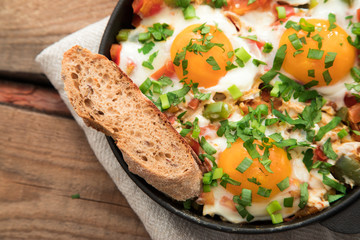 Shakshuka with eggs, tomato, and parsley in a iron pan. Shakshuka - traditional israeli tomato stew with eggs