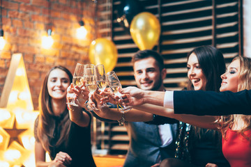Cheers! Friends with glasses of champagne during party celebration