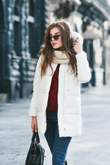 Outdoor portrait of young beautiful fashionable woman wearing stylish white winter puffer coat. Model walking in street of the city. Female fashion concept