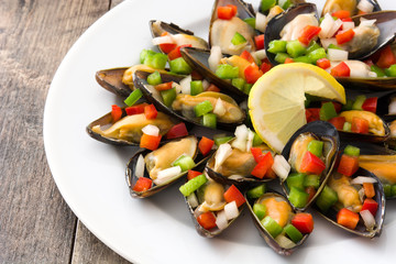 Steamed mussels with peppers and onion on wooden table