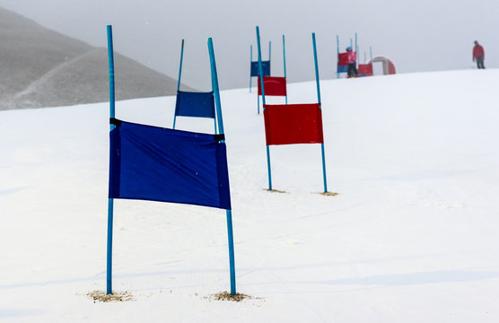 Children skiing slalom racing track with blue and red gates.