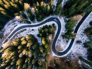 Spoed Fotobehang Luchtfoto Aerial view of snowy forest with a road. Captured from above with a drone