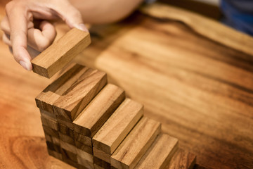 Business man hand put wooden blocks arranging stacking for development as step stair, Concept of growth and success plan
