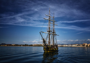 Old wooden sailing ship in the sea on summer day