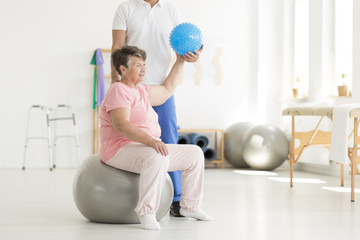 Senior woman raising blue ball