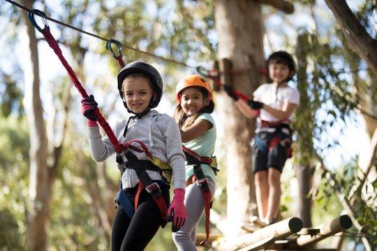Portrait of happy kids crossing zip line