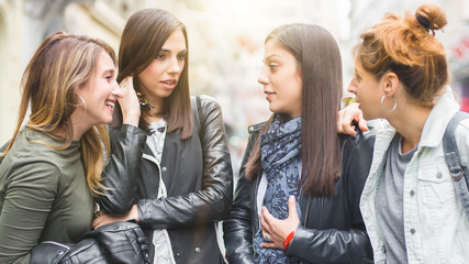 Portrait of four pretty girl friends, gossip on the street