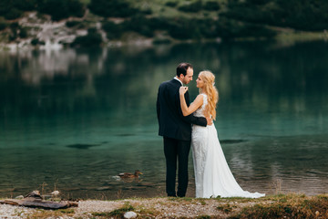 Beautiful wedding couple near the lake in the Alps