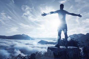 Person auf einem Gipfel über den Wolken