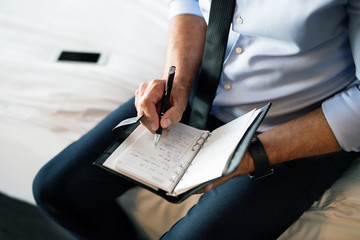 Mature businessman making notes in a hotel room.