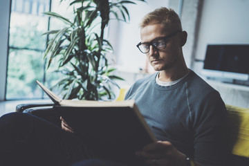 Portrait handsome young man wearing glasses casual clothes holding book hands.Man sitting in vintage armchair modern loft studio reading book. Blurred background.Horizontal.