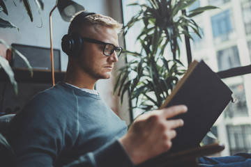 Handsome young man wearing glasses casual clothes.Man sitting in vintage armchair modern loft studio, reading book and relaxing whit headphone music. Blurred background.Horizontal.Cropped.