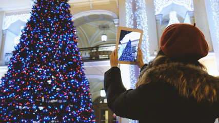 Attractive young girl taking pictures with a tablet Christmas tree