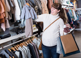 Woman choosing clothes for baby