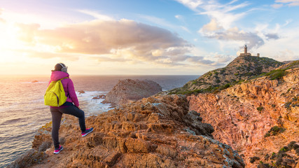 Female traveller in a lilac jacket on the top of the cliff looks out into distance to the lighthouse and admiring the view