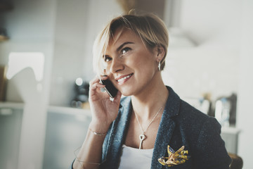 Attractive businesswoman talking with partner via modern telephone while writing some information in note book while sitting at living room in hotel.Blurred background.