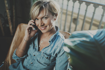 Smiling young woman wearing casual clothes and talking on smartphone device while spending relax time in vacation travel.Attractive woman owner communicating on cellular.Blurred background.