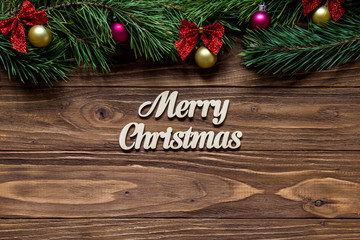 Merry Christmas on the center of the wooden background with pine tree branches on the top of the screen