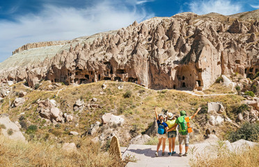 Group of three active friends backpackers tourists hiking among colorful rocks by desert path trail. Concept of travel to middle east